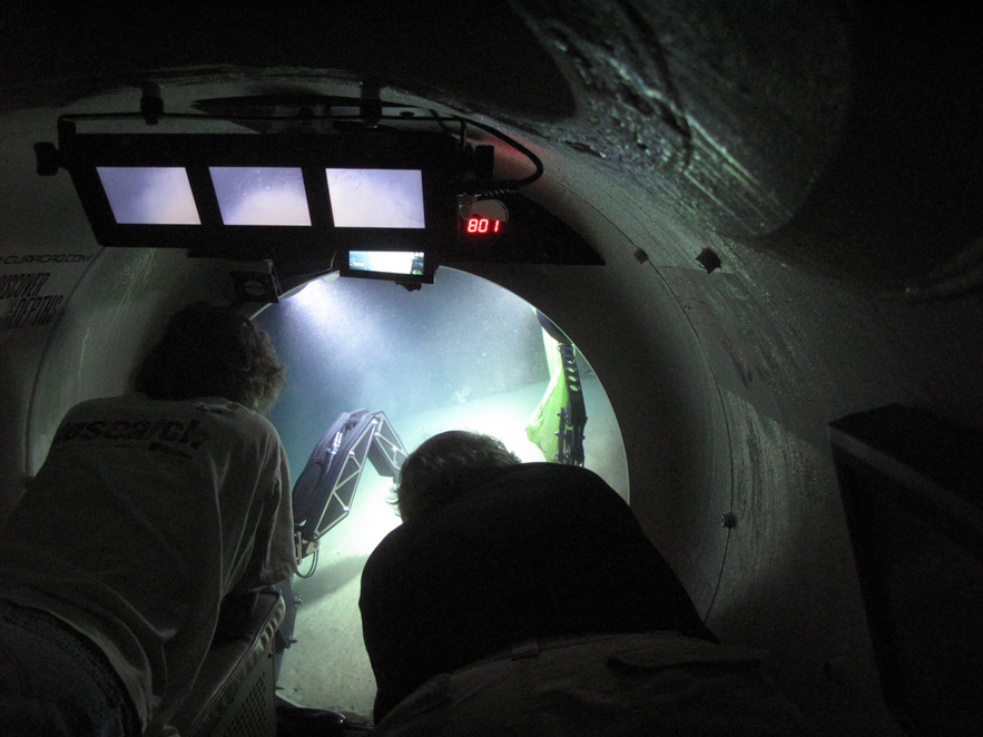 Two scientists peer out into the ocean from inside the Curasub, a 5-person submersible <div class='credit'><strong>Credit:</strong> Two scientists peer out into the ocean from inside the Curasub, a 5-person submersible </div>