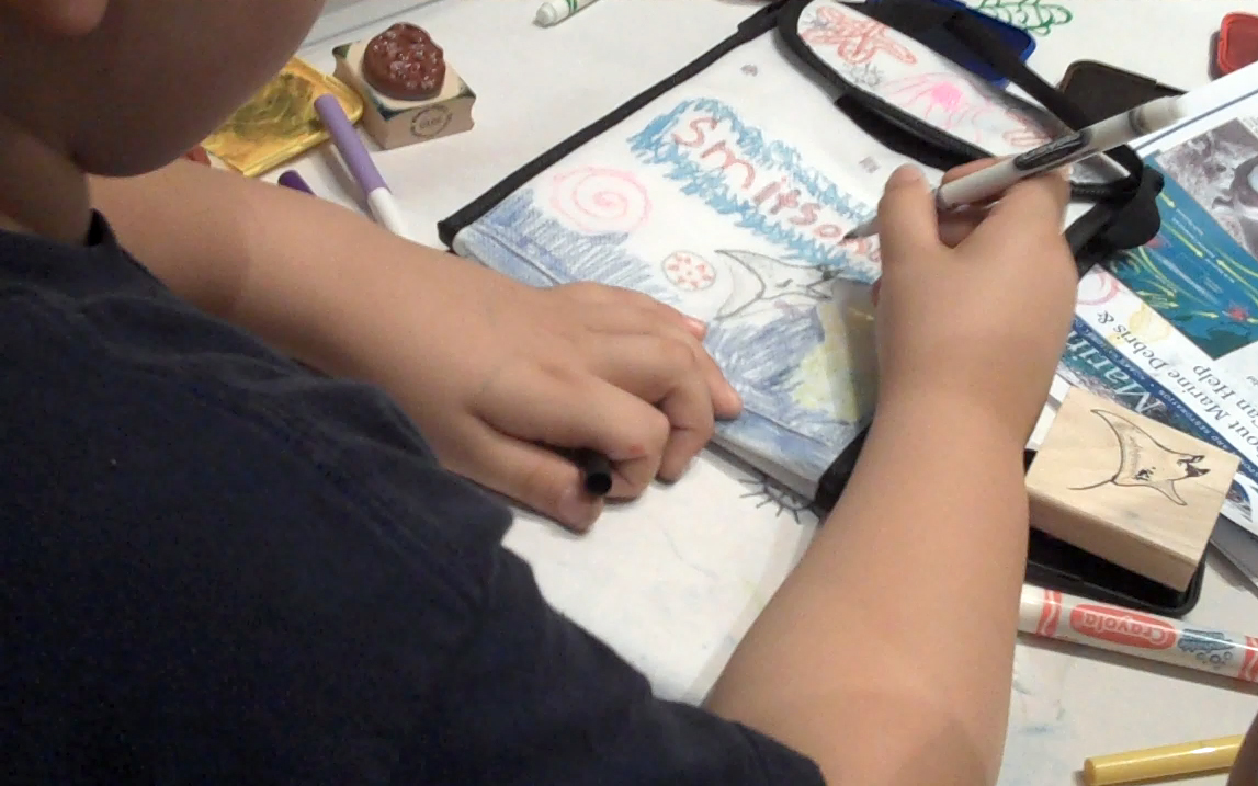 A student uses a marker to decorate a reusable lunch bag with ocean creatures<div class='credit'><strong>Credit:</strong> A student uses a marker to decorate a reusable lunch bag with ocean creatures</div>