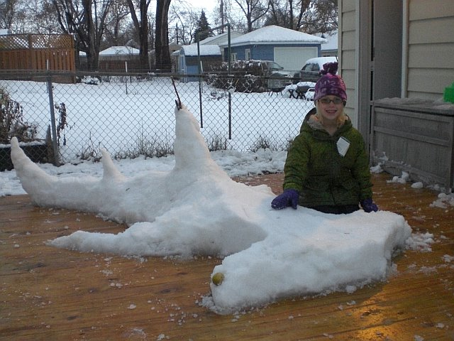 A girl poses with her shark snow sculpture.<div class='credit'><strong>Credit:</strong> A girl poses with her shark snow sculpture.</div>
