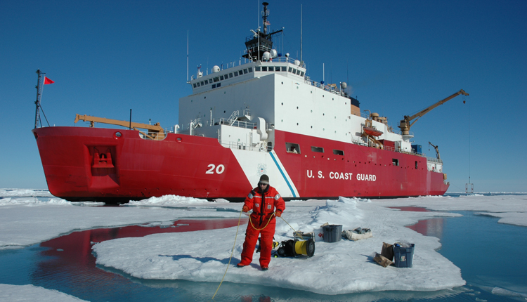 A dive tender monitors divers below the ice.<div class='credit'><strong>Credit:</strong> A dive tender monitors divers below the ice.</div>