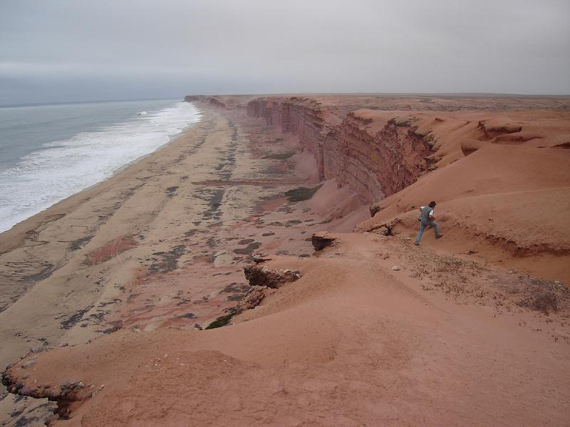Sandy cliffs of coastal Angola with waves crossing on the shore.