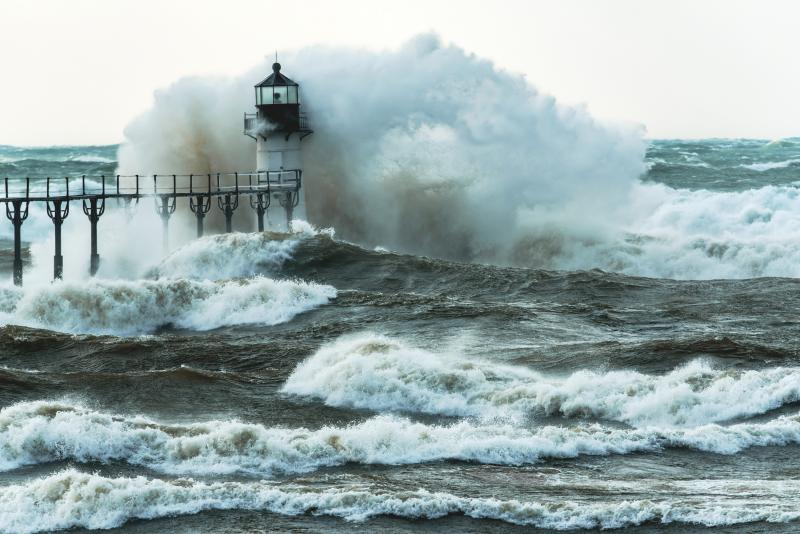 a large storm wave crashes over a lighthouse at the end of a pier