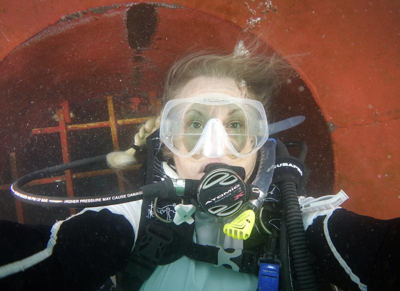 "Laurie takes a break collecting invasive species to snap a ""selfie"" while under the hull of a cargo ship."