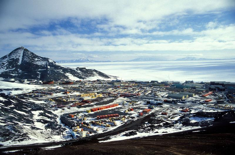 A view of McMurdo Station with a frozen Ross Sea in the background.