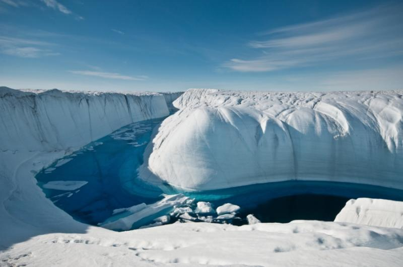 A summertime channel carries melted ice to the sea. Antarctica and Greenland lose around 350 billion tons of ice each year from such melting.