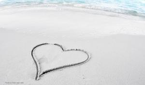 A photo of a beach with a heart inscribed in the sand.