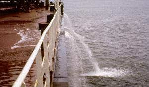 A large ship flushes water from its ballast tanks while at sea