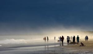 A beach scene with groups of people walking in the water and playing with the sand.