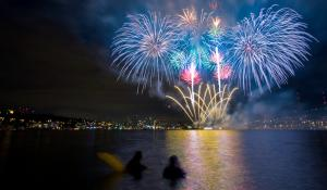 Colorful fireworks go off over the water.