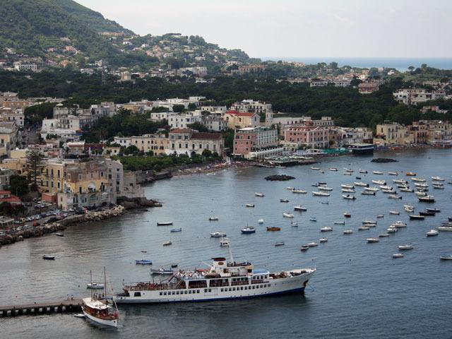 A photo of a seaside town with boats docked in the harbor and buildings along the shore.