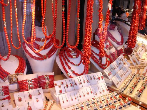 a display case of red coral jewelry containing necklaces, earrings, bracelets, and rings