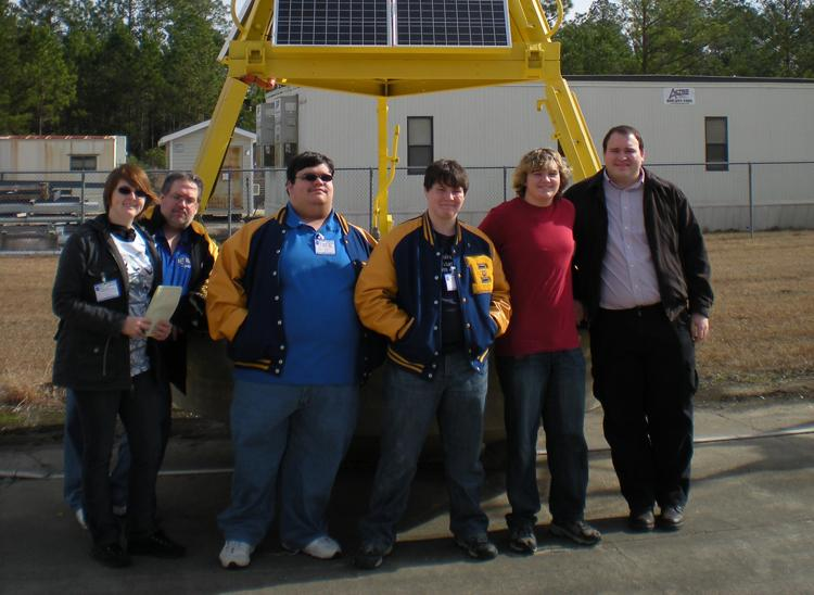 Students studying climate change pose for a photo at a NOAA facility.