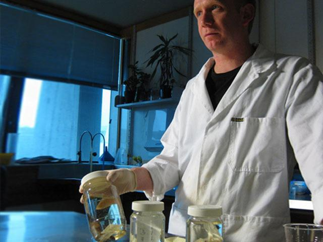 A scientist in a white lab coat stands in laboratory holding a jar of marine specimens.