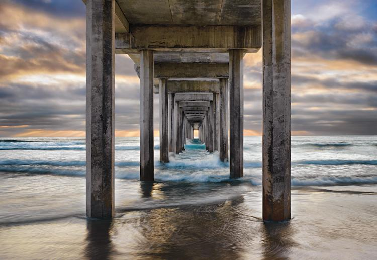 """This composition is a blend of nature and architecture. Shooting beneath the structure to get a unique perspective, I waited for days for a thick mist to lift and reveal the backlighting and color I needed to frame the pier's converging lines. I was f"
