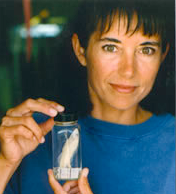 Carole Baldwin holding a preserved fish in a jar.