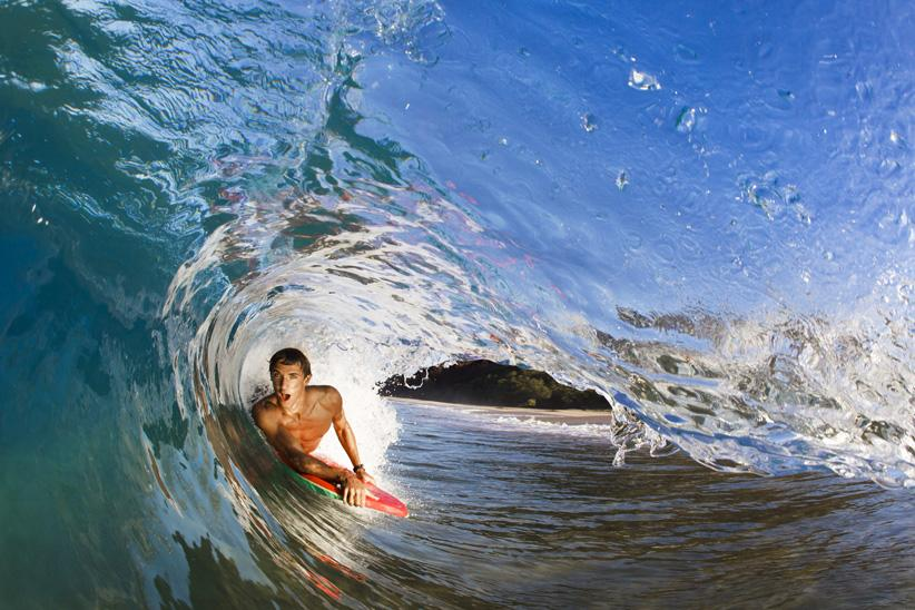 A male surfer catching a wave in Hawaii