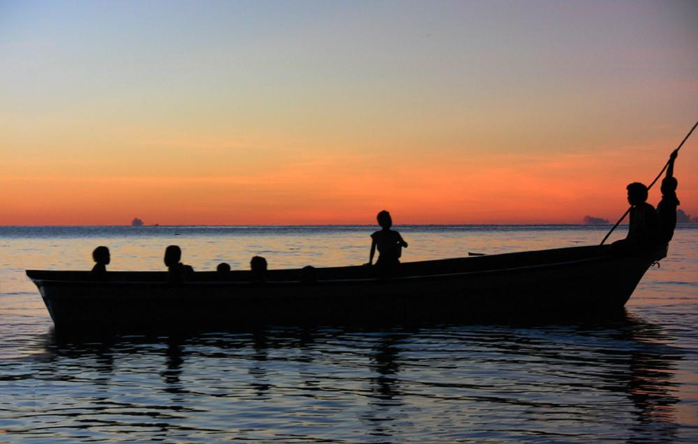 A silhouette of a small boat carrying 8 passengers on tranquil water, with a pink horizon.