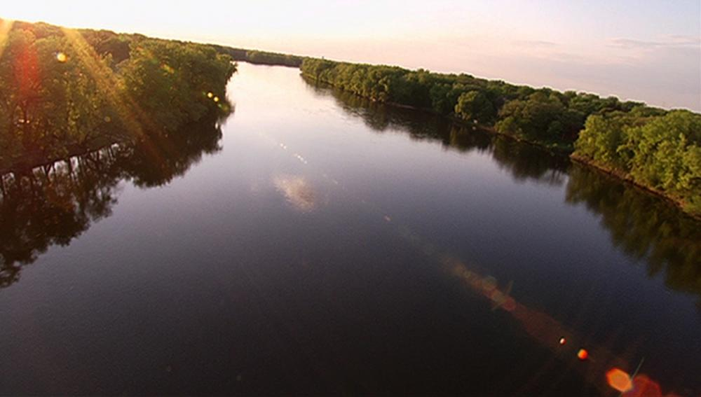 An aerial shot of a tree-lined section of the Mississippi River at sunset.