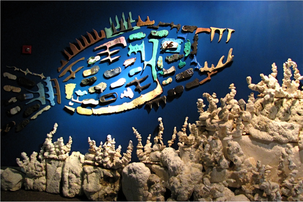 A fish made from pieces of plastic found on the beach swims above a bleached reef made of Styrofoam.