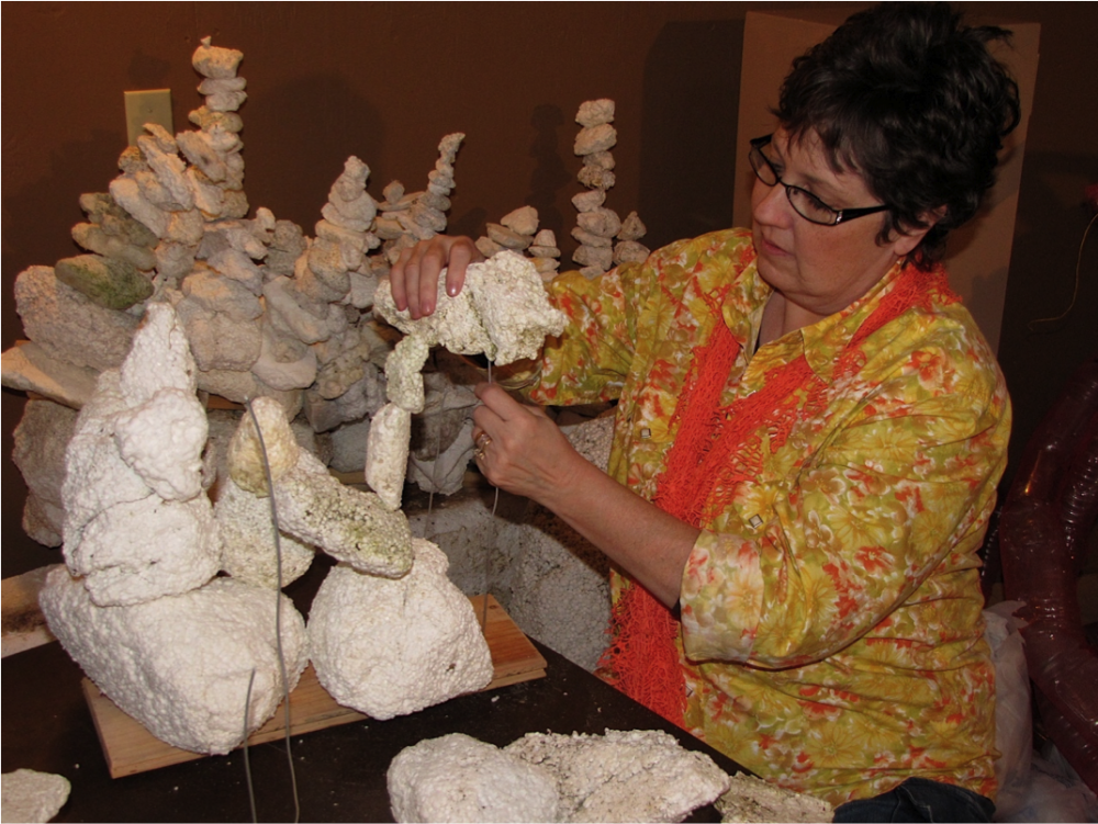 A volunteer puts together the bleached coral reef by stacking pieces of Styrofoam onto wire.