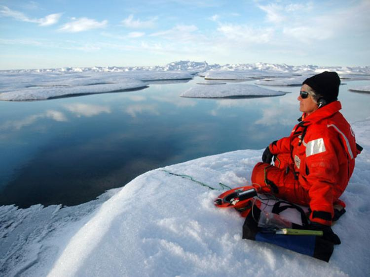 A marine mammal scientist listens for bowhead whales using an underwater hydrophone.