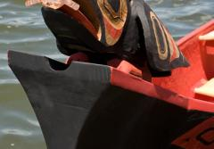 With the sun in its beak, the canoe's raven figurehead points the way.