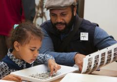 An adult and child visitor participate in an activity at the Natural History Museum