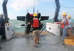 A large, black instrument is hauled onto a ship's deck by researchers wearing hard hats and life vests.