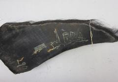 A baleen plate with a drawing of a ship in paint