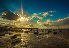 boats sit in the mud at low tide underneath a sunset