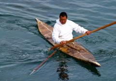 a man in a white hooded sweatshirt paddles in a skin boat kayak
