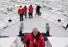 A photo of oceanographer Xavier Pastor aboard an Oceana research vessel surrounded by ice in the Baltic Sea