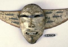 This mask sits atop a decorative breastplate with images of whaling crews in skin boats called umiaks.