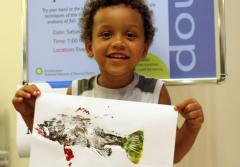 A young visitor holds up his painted fish Gyotaku fish print at the Smithsonian's National Museum of Natural History
