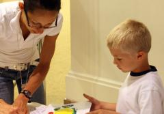 A teacher and a young boy paint a fish mold to create a Gyotaku style print