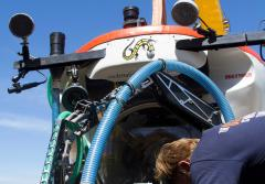 Submarine pilot Bruce Brandt secures ARMS to the outside of the submersible Curasub so it can deploy ARMS on the seafloor.