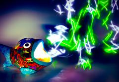 A light painted image of a hand-painted ceramic fish with light emitting from its mouth