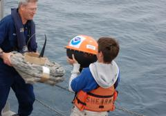 A student helps deploy one of his school's adopted drifters for NOAA's Adopt a Drifter Program.