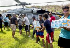 Volunteers unloading water from helicopter