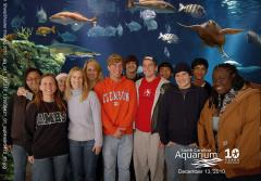 Students pose in front of an aquarium tank with fish.