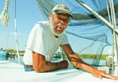 A Gulf Coast resident sits on his boat, smiling for the camera.
