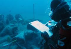 A researcher takes notes at the site of an ancient shipwreck recently discovered in Mazotas, Cyprus. The ship went down in the 4th century B.C. loaded with expensive and sought-after wine from Greece.