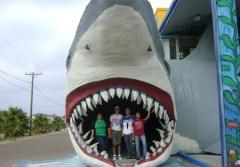 Students pose in the mouth of a giant model of a shark.