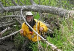 Botanist Dennis Whigham stands in a forested wetland with field gear.