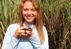 Alexis Temkin stands in marsh grass holding a reptile.