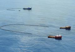 boats sweeping up the oil slick