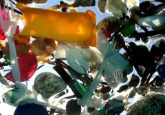 A photo of plastic trash floating in the water, taken from below the surface.