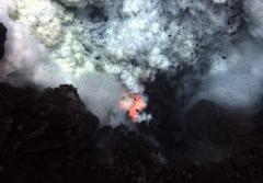Red hot magma and ash erupt from an underwater volcano.