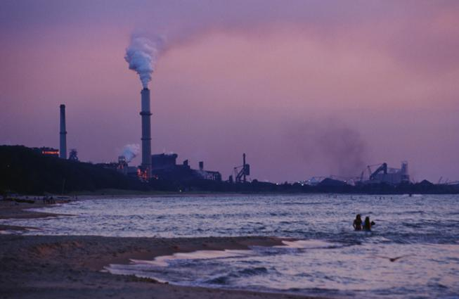 Swimmers brave the waters in the shadow of a coal-fired power plant.  Coal plants like this one emit CO2 into our atmosphere which is warming the planet and altering the chemistry of the ocean.